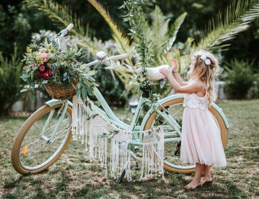 Vélo bohème avec la petite fille de cérémonie pieds nus